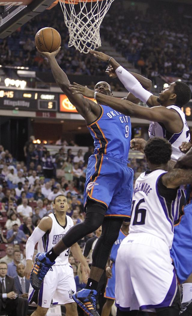 Oklahoma City Thunder center Serge Ibaka, center, of the Congo, drives to the basket against Sacramento Kings forward Jason Thompson, right, as Kings' Ray McCallum, left, and Ben McLemore foreground, look on during the first quarter against the Sacramento Kings in an NBA basketball game, Tuesday, April 8, 2014, in Sacramento, Calif. (AP Photo/Rich Pedroncelli)