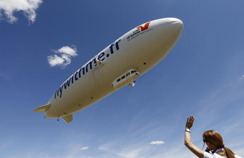 A ground crew member waves as a semi-rigid and helium-filled Zeppelin NT departs from a field at an airport outside Cergy-Pontoise, near Paris, August 4, 2013. The Zeppelin NT is powered by three pivoting motors and measures 75.1 meters (246 ft) long, (as long as an Airbus 380), 17.4 meters (57 feet) high, and 19.5 (64 feet) meters wide. It also has a cabin that fits 12 passengers and will fly tourists at an altitude of 300 meters (984 feet) over the countryside. According to the company's media release, Airship Paris, which runs the Zeppelin NT, will propose three different flights for tourists in the Paris region, including the Chateau of Versailles, Giverny, and Chantilly and the valley of the Impressionists. REUTERS/John Schults (FRANCE - Tags: TRANSPORT SOCIETY TRAVEL TPX IMAGES OF THE DAY)