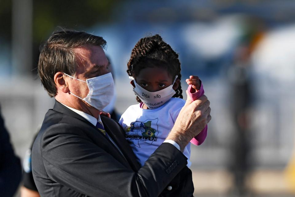 Brazilian President Jair Bolsonaro holds a girl in his arms, both wearing face masks, during the flag-raising ceremony before a ministerial meeting at the Alvorada Palace in Brasilia, on May 12, 2020, amid the new coronavirus pandemic. (Photo by EVARISTO SA / AFP) (Photo by EVARISTO SA/AFP via Getty Images)