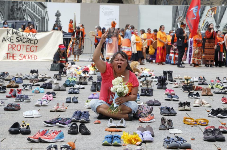 A woman sits with her legs crossed surrounded by hundreds of children's shoes