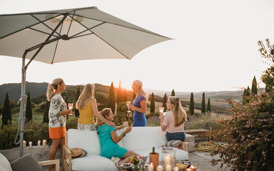 Friends drinking wine on villa terrace with view - Getty