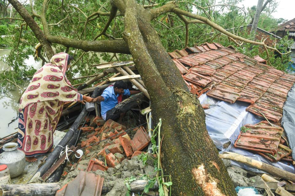 Villagers salvage items from their house damaged by cyclone Amphan in Midnapore, West Bengal, on May 21, 2020. - The strongest cyclone in decades slammed into Bangladesh and eastern India on May 20, sending water surging inland and leaving a trail of destruction. (Photo by DIBYANGSHU SARKAR/AFP via Getty Images)
