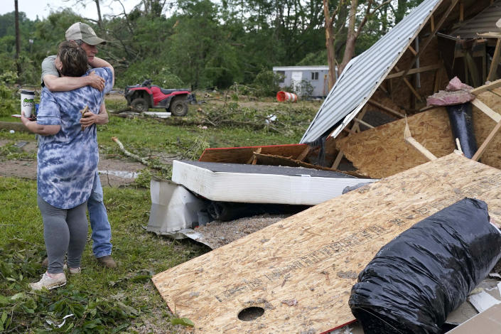 Image: A neighbor hugs Vickie Savell next to the remains of her new mobile home early on May 3, 2021, in Yazoo County, Miss. (Rogelio V. Solis / AP)