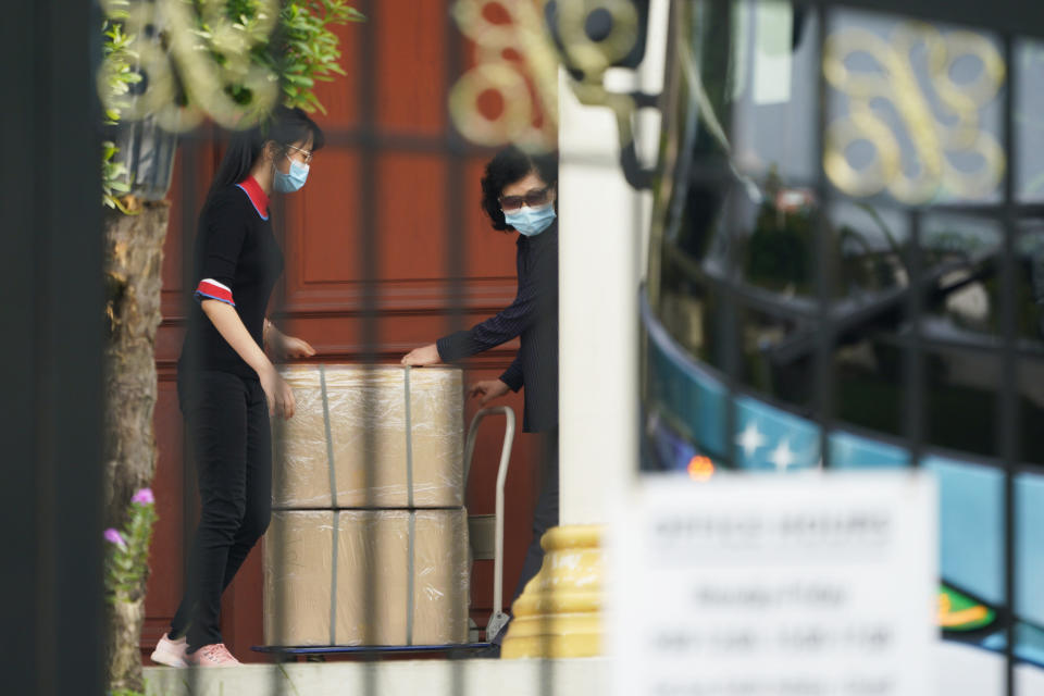 Unidentified persons load boxes to a bus at the North Korean Embassy in Kuala Lumpur, Malaysia, Sunday, March 21, 2021. Malaysia on Friday ordered all North Korean diplomats to leave the country within 48 hours, an escalation of a diplomatic spat over Malaysia's move to extradite a North Korean suspect to the United States on money laundering charges. (AP Photo/Vincent Thian)