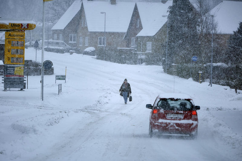 A woman walks the main road in the village of Klemensker on the Danish island of Bornholm in the Baltic Sea, as snow and heavy wind hit Denmark from the East, Tuesday Feb. 27, 2018. Much of Europe is currently experiencing low temperatures due to a blast of icy air from the northeast. (Pelle Rink/Ritzau Scanpix via AP)