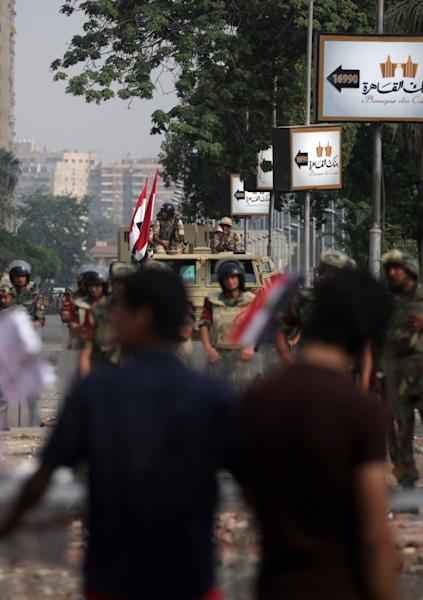 Supporters of ousted President Mohammed Morsi protest as army soldiers guard at the Republican Guard building in Nasr City, Cairo, Egypt, Tuesday, July 9, 2013. Egyptian security forces killed dozens of supporters of Egypt's ousted president in one of the deadliest single episodes of violence in more than two and a half years of turmoil. The toppled leader's Muslim Brotherhood called for an uprising, accusing troops of gunning down protesters, while the military blamed armed Islamists for provoking its forces. (AP Photo/Khalil Hamra)