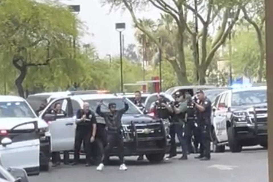 In this image from video provided by Neil Betrue, a suspect is surrounded by police before being taken into custody after multiple shootings in Surprise, Ariz., on Thursday, June 17, 2021. Investigators on Friday, June 18 were trying to determine why a gunman opened fire on vehicles and pedestrians for some 90 minutes across metropolitan Phoenix, leaving one person dead and a dozen others injured in the string of drive-by shootings. Authorities believe the man they arrested after the shootings on Thursday acted alone. His identity hasn't been released.. (Neil Betrue via AP)