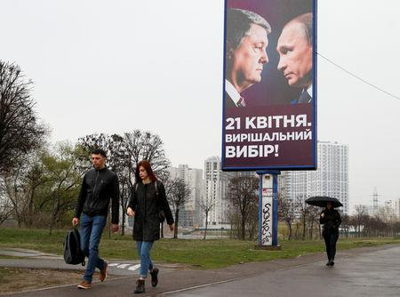 People walk past an election campaign poster with portraits of Ukrainian President and presidential candidate Petro Poroshenko and Russian President Vladimir Putin in Kiev, Ukraine April 11, 2019.  REUTERS/Valentyn Ogirenko