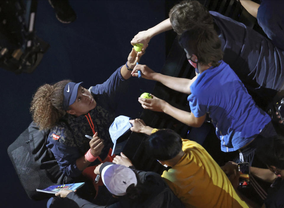 Japan's Naomi Osaka signs autographs after defeating United States' Jennifer Brady in the women's singles final at the Australian Open tennis championship in Melbourne, Australia, Saturday, Feb. 20, 2021.(AP Photo/Hamish Blair)