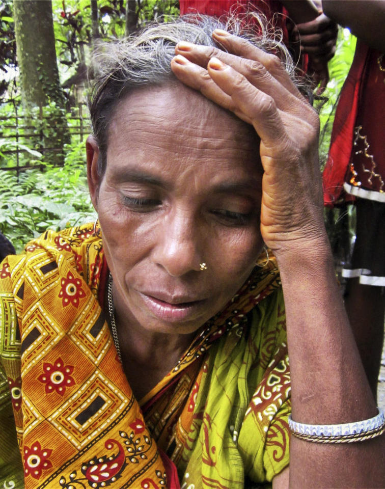 ADD STATE - An Indian woman from Dimol village reacts as she leaves her home following ethnic clashes in Kokrajhar, India, Tuesday, July 24, 2012. Government troops sent to quell communal clashes over land rights in the northeast Indian state of Assam were under orders Tuesday to shoot suspected rioters on sight after some 21 people were killed in machete attacks and dozens of homes were burned to the ground. (AP Photo)