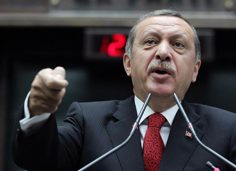 Turkey's Prime Minister Recep Tayyip Erdogan addresses his lawmakers at the parliament in Ankara, Turkey, Tuesday, June 18, 2013. After weeks of confrontation with police, sometimes violent, Turkish protesters are using a new form of resistance: standing silently. The development started late Monday when a solitary man, Etrdem Gunduz, began standing in passive defiance against Prime Minister Recep Tayyip Erdogan's authority at Istanbul's central Taksim Square.(AP Photo)