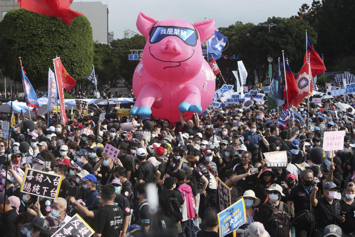 """People hold a pig model with """"I am a ractopamine pig"""" written on it during a protest in Taipei, Taiwan, Sunday, Nov. 22. 2020. Thousands of people marched in streets on Sunday demanding the reversal of a decision to allow U.S. pork imports into Taiwan, alleging food safety issues. (AP Photo/Chiang Ying-ying)"""