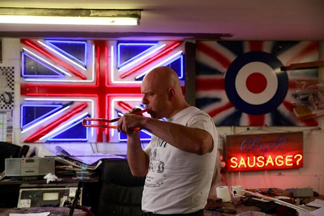 <p>Neon Bender Nick Ellwood blows into glass tubes to maintain their shape as he bends them while making neon artworks in God's Own Junkyard workshop in Rainham in God's Own Junkyard in London, Britain, May 17, 2017. (Photo: Russell Boyce/Reuters) </p>
