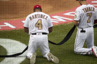 Washington Nationals manager Dave Martinez (4) and shortstop Trea Turner (7) kneel and hold a piece of black fabric before an opening day baseball game against the New York Yankees at Nationals Park, Thursday, July 23, 2020, in Washington. (AP Photo/Alex Brandon)