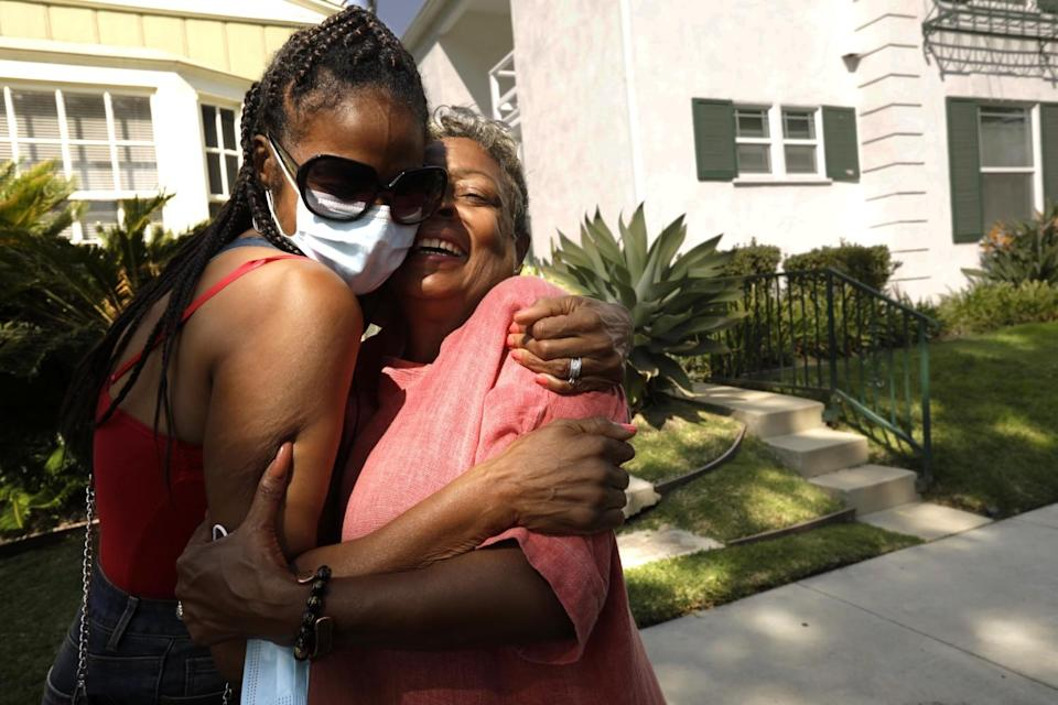 Crystal Bright, right, receives a hug from her sister Vanessa Smith-Robinson in front of Bright's home,