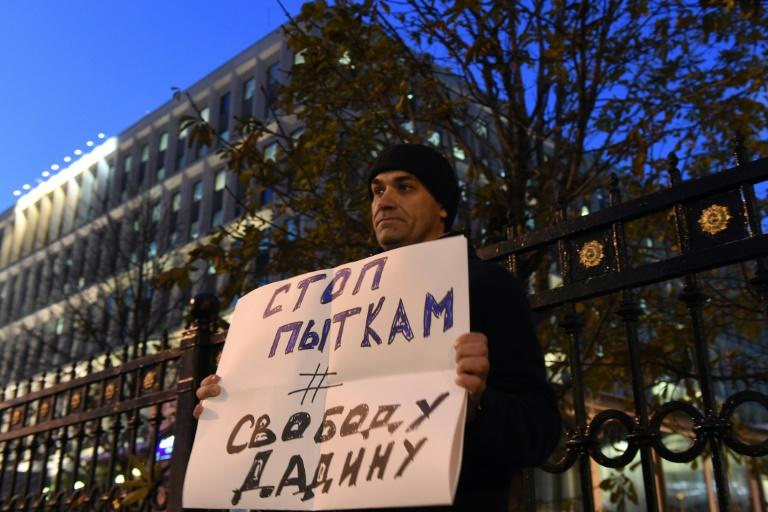 "A man holds a placard reading ""Stop torture, Freedom for Dadin"" as he pickets Russia's Federal Penitentiary Service headquarters in Moscow"