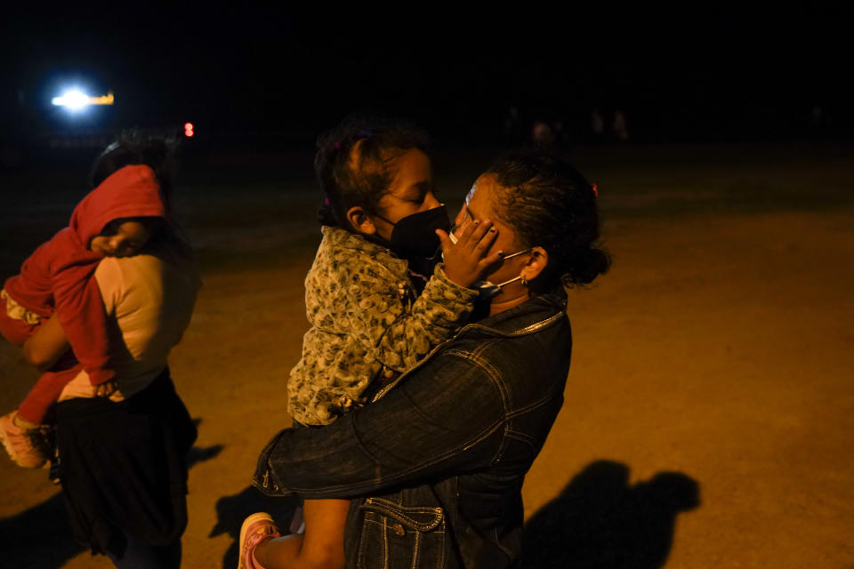 A migrant child from Honduras kisses her mother through masks at an intake area after they turned themselves in upon crossing the U.S.-Mexico border, late Tuesday, May 11, 2021, in La Joya, Texas. The U.S. government continues to report large numbers of migrants crossing the U.S.-Mexico border with an increase in adult crossers. But families and unaccompanied children are still arriving in dramatic numbers despite the weather changing in the Rio Grande Valley registering hotter days and nights. (AP Photo/Gregory Bull)