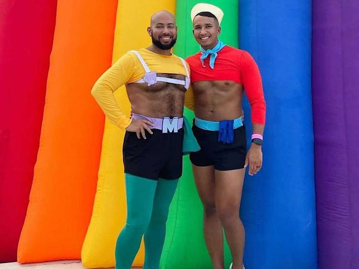 """A man dressed as Mermaid Man poses in front of a rainbow backdrop next to a man dressed as Barnacle Boy from """"Spongebob Squarepants."""""""