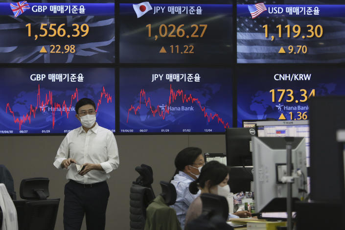 A currency trader passes by screens showing foreign exchange rates at the foreign exchange dealing room of the KEB Hana Bank headquarters in Seoul, South Korea, Tuesday, May 4, 2021. Asian shares were mixed Tuesday after strong corporate earnings and economic data lifted stocks on Wall Street. (AP Photo/Ahn Young-joon)