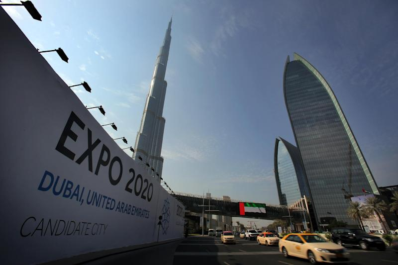 In this Wednesday Nov. 20, 2013, with the Burj Khalifa, the world's tallest building in the background, vehicles pass by a billboard advertising Dubai as a candidate city for the Expo 2020 in Dubai, United Arab Emirates. The logo for Dubai's bid to host the Expo 2020 reflects a push by the city's leaders to avert another financial crisis like the one that brought the city to its knees in 2008. Dubai saw property values slashed by more than half and the city's government needed a $10 billion bailout from oil-rich neighbor Abu Dhabi in 2009. (AP Photo/Kamran Jebreili)