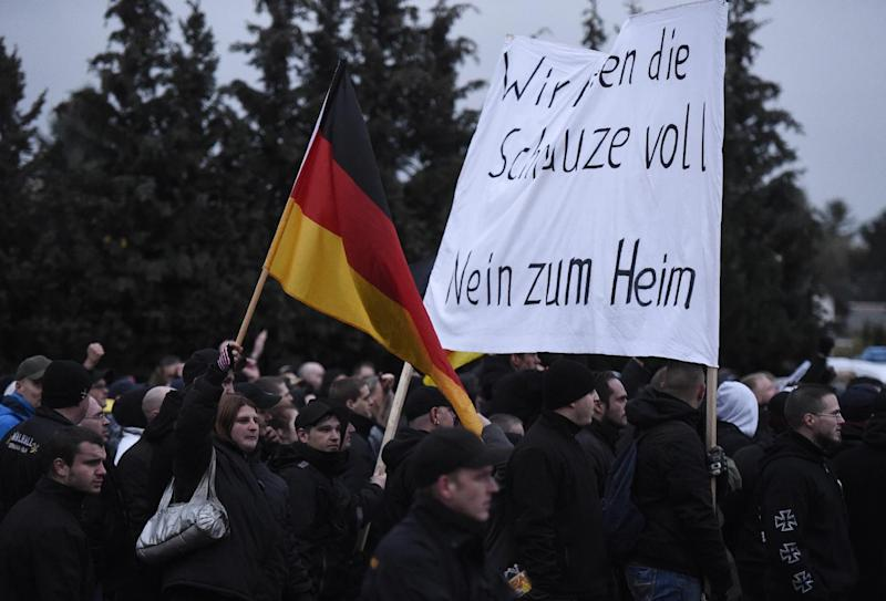 People hold a banner reading 'We have had enough of it, no to an accomodation' during a demonstration against the construction of residential units for asylum seekers and refugees in Berlin's Marzahn-Hellersdorf district on November 22, 2014 (AFP Photo/Odd Andersen)