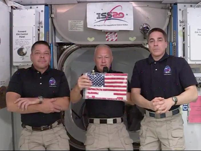 <br>Doug Hurley holds up the flag during a press call with Bob Behnken (left) and astronaut Chris Cassidy (right) aboard the International Space Station, June 1, 2020.