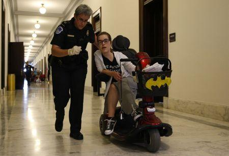 A protester is escorted away by police after being arrested during a demonstration outside Senate Majority Leader Mitch McConnell's constituent office after Senate Republicans unveiled their healthcare bill on Capitol Hill in Washington, U.S., June 22, 2017. REUTERS/Kevin Lamarque