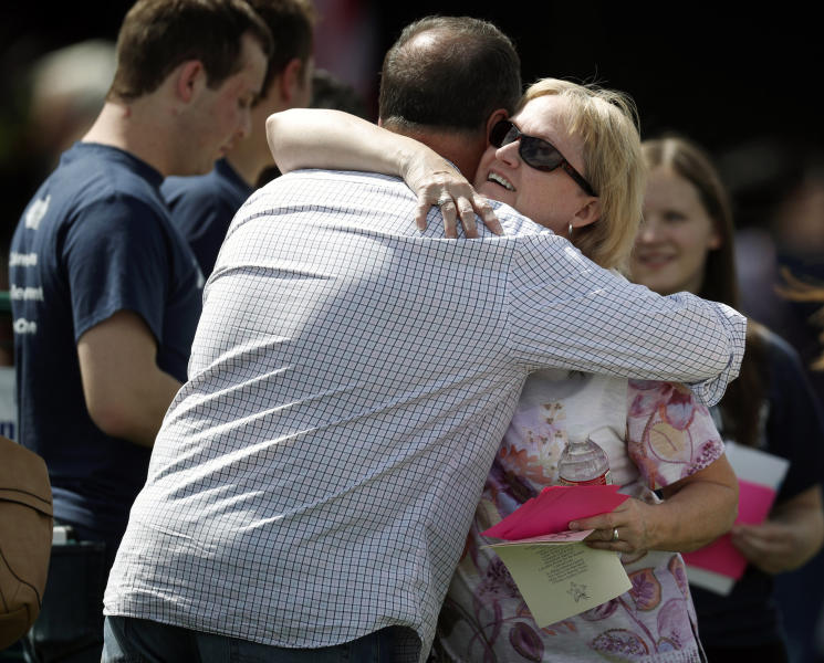 Attendees hug before a program for the victims of the massacre at Columbine High School 20 years ago Saturday, April 20, 2019, in Littleton, Colo. (AP Photo/David Zalubowski)