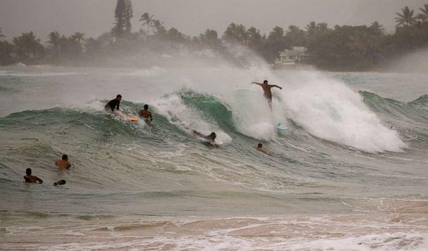 PHOTO: Surfers take on large waves generated by Hurricane Douglas at Laie Beach Park, Sunday, July 26, 2020, in Laie, Hawaii. (Eugene Tanner/AP Photo)