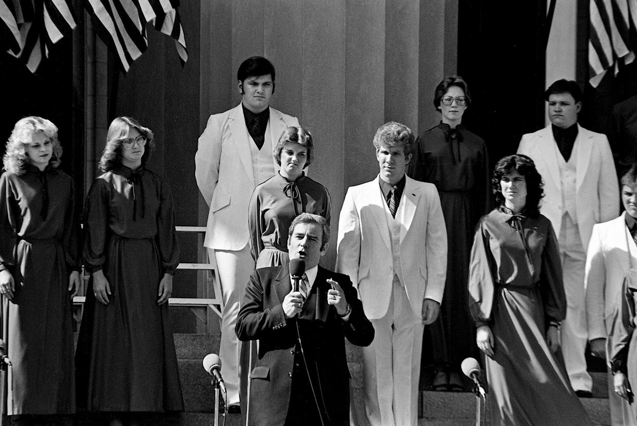 "Backed by 32 choreographed singers in red, white and blue, the Rev. Jerry Falwell, pastor of the 17,000-member Thomas Road Baptist Church in Lynchburg, Va., presides over an ""I Love America"" rally at Legislative Plaza in Nashville on Oct. 15, 1979."