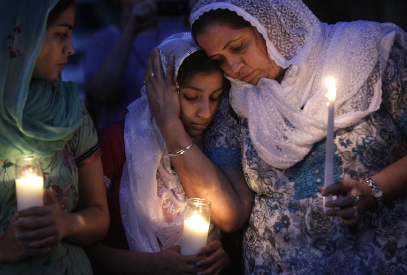 FOR USE AS DESIRED WITH SIKH TEMPLE SHOOTING ANNIVERSARY STORIES - FILE - In this Aug. 6, 2012, file photo worshipers from the Sikh community gather for a candle light vigil after prayer services in Brookfield, Wis. Twelve months ago, a white supremacist walked into a the temple and opened fire on worshippers he didn't know, killing six and devastating a Sikh community whose religion is based on peace and forgiveness. Monday is the one-year anniversary of the shooting. (AP Photo/M. Spencer Green, File)
