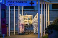 Medical workers in overalls stretch a patient under intensive care into the newly built Columbus Covid 2 temporary hospital to fight the new coronavirus infection, on March 16, 2020 at the Gemelli hospital in Rome. (Photo by ANDREAS SOLARO / AFP) (Photo by ANDREAS SOLARO/AFP via Getty Images)