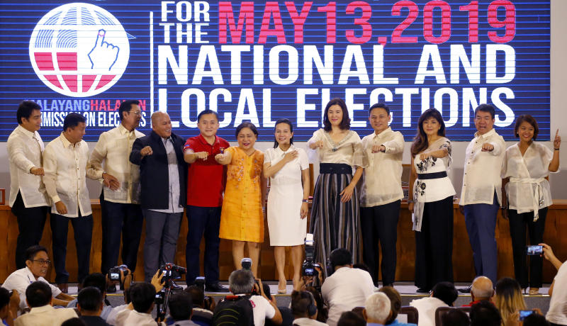Twelve newly-proclaimed senators gesture their own political party symbols during a ceremony at the Commission on Elections in suburban Pasay city, south of Manila, Philippines Wednesday, May 22, 2019. They are, from left, Senators Bong Revilla, Francis Tolentino, Lito Lapid, Ronald Dela Rosa, Christopher Go, Cynthia Villar, Grace Poe, Pia Cayetano, Sonny Angara, Imee Marcos, Aquilino Pimentel and Nancy Binay. (AP Photo/Bullit Marquez)