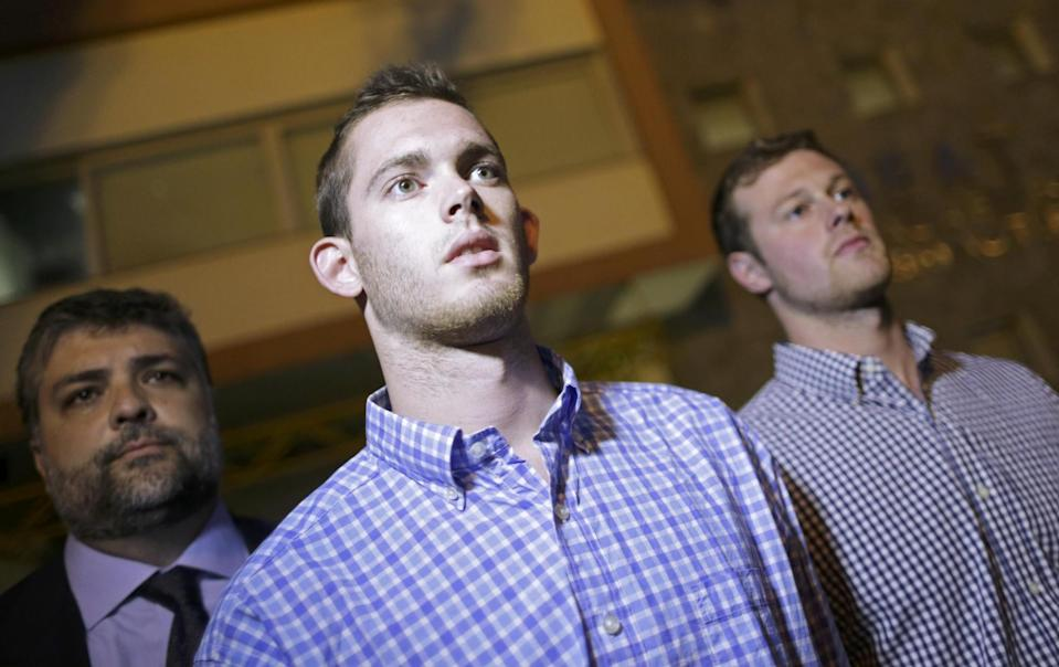 American swimmers Gunnar Bentz and Jack Conger leave the police station Thursday night. (Reuters)