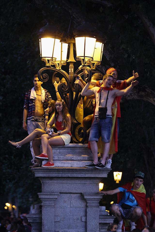 MADRID, SPAIN - JULY 02: Supporters of Spain's national football team climb onto a street light to view their team's players as they return to Madrid following their victory in the UEFA EURO 2012 football championships on July 2, 2012 in Madrid, Spain. Spain beat Italy 4-0 in the UEFA EURO 2012 final match in Kiev, Ukraine, on July 1, 2012. (Photo by Oli Scarff/Getty Images)