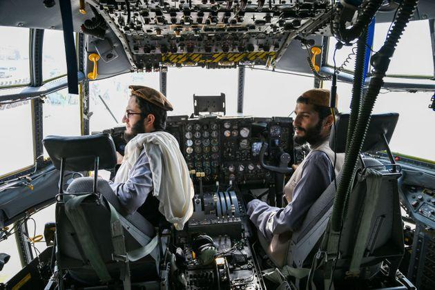 <strong>Taliban fighters sit in the cockpit of an Afghan Air Force aircraft at the airport in Kabul.</strong> (Photo: WAKIL KOHSAR via Getty Images)