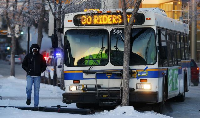 """A man walks by a bus with an advertisement """"Go Rider Go"""" after it crashed into a pole on a cold day in Regina, Saskatchewan, November 21, 2013. The Hamilton Tiger-Cats will play the Saskatchewan Roughriders in the CFL's 101st Grey Cup in Regina November 24, 2013. REUTERS/Todd Korol (CANADA - Tags: SPORT FOOTBALL TRANSPORT)"""