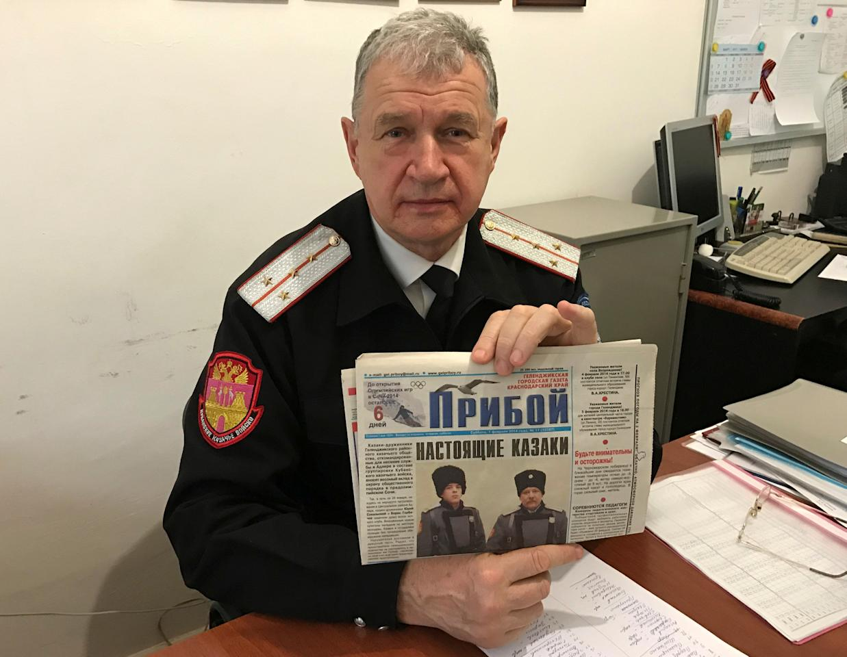 Russian Cossack commander Vladimir Bagliy shows a local newspaper with a picture of his fellow Cossack Yuri Sokalsky (R) killed near the Syrian city of Palmyra, in the Black Sea town of Gelendzhik, Russia, March 16, 2017. Picture taken March 16, 2017. REUTERS/Maria Tsvetkova  TO MATCH INSIGHT  MIDEAST-CRISIS/SYRIA-RUSSIA-CASUALTIES