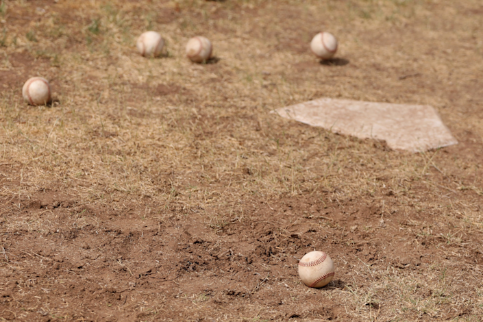 SCOTTSDALE, ARIZONA - JUNE 05: Baseballs are seen on the backyard dirt around a home plate.