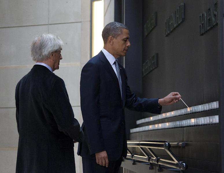 President Barack Obama, accompanied by Nobel Peace Prize laureate and Holocaust survivor Elie Wiesel, light candles in the Hall of Remembrance as they toured the Holocaust Memorial Museum in Washington, Monday, April 23, 2012. (AP Photo/Carolyn Kaster)