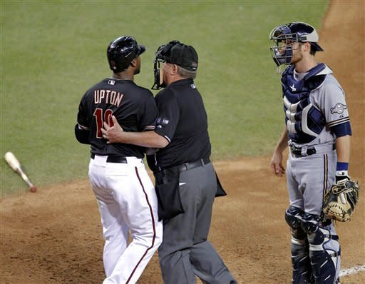 Arizona Diamondbacks' Justin Upton (10) is held back by home plate umpire Derryl Cousins as Milwaukee Brewers catcher Jonathan Lucroy watches after Upton was hit by a pitch during the third inning of a baseball game, Saturday, May 26, 2012, in Phoenix. (AP Photo/Matt York)