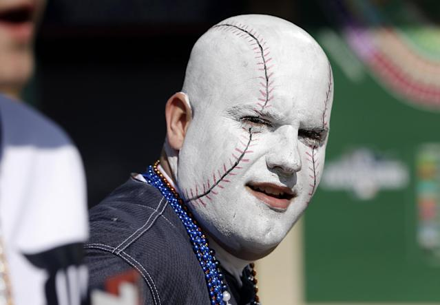 George Uhl of Sterling Heights, Mich., is made up to look like a baseball before a baseball game between the Detroit Tigers and the Kansas City Royals in Detroit, Monday, March 31, 2014. (AP Photo/Carlos Osorio)