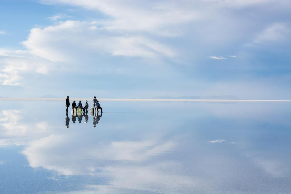 <p>Explorers appear to stand on water at the salt flats of Bolivia. (Photo: Hideki Mizuta/Caters News) </p>