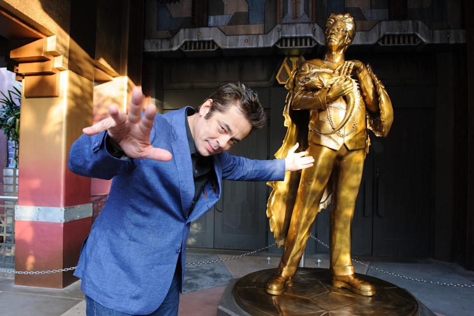 <p>Oscar winner Benicio Del Toro hams it up in front of a golden statue of his character Taneleer Tivan, a.k.a. The Collector, in the foyer of the new ride. (Photo: Disneyland Resort) </p>