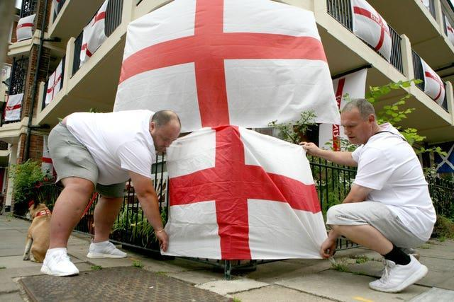 Chris Dowse (left) and Alan Putman, secure a flag on the Kirby Estate in Bermondsey, south London (Luciana Guerra/AP)