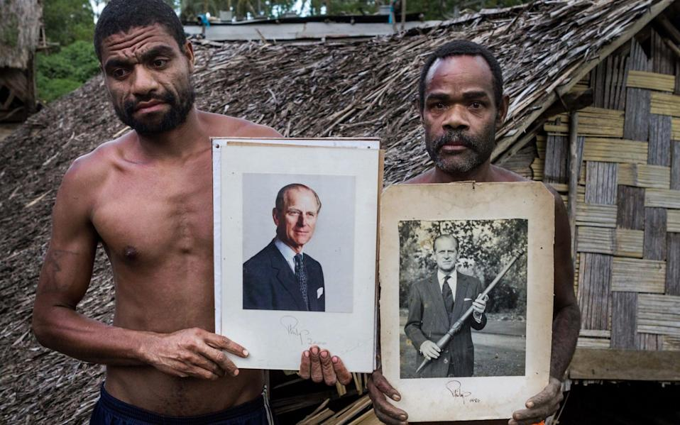 Men from the village of Yaohnanen hold portraits of the Duke, which he gave the village in 2012 - Roman Kalyakin/Corbis