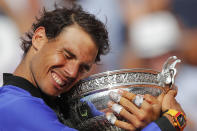 FILE - In this June 11, 2017, file photo, Spain's Rafael Nadal holds the trophy as he celebrates winning his tenth French Open title, against Switzerland's Stan Wawrinka, at Roland Garros stadium, in Paris, France. Federer leads the list with 20 Grand Slam singles titles. Nadal has 19. Novak Djokovic has 16. (AP Photo/Christophe Ena, File)