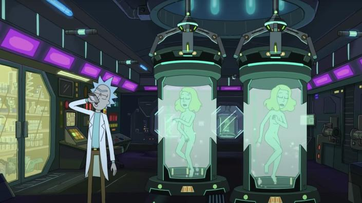 Rick drinks from a flask in his lab inf ront of two tanks of water holding his daughter Beth