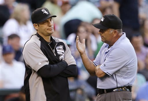 Chicago White Sox manager Robin Ventura, left, talks with umpire Dale Scott about a double by Seattle Mariners' Nick Franklin, originally called a home run, that scored a run in a run in the third inning of a baseball game Tuesday, June 4, 2013, in Seattle. (AP Photo/Elaine Thompson)