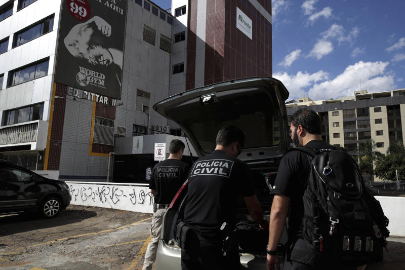 Criminal police officers arrive to retrieve the body of Debora Tereza Correia, murdered today by her boyfriend at the city education department in Brasilia, Brazil, Monday, May 20, 2019. Brazilian officials say a police officer shot his ex-girlfriend to death in her office at the city education department in Brazil's capital and then killed himself. Forty-three-year-old Debora Tereza Correia was shot three times and died immediately. (AP Photo/Eraldo Peres)